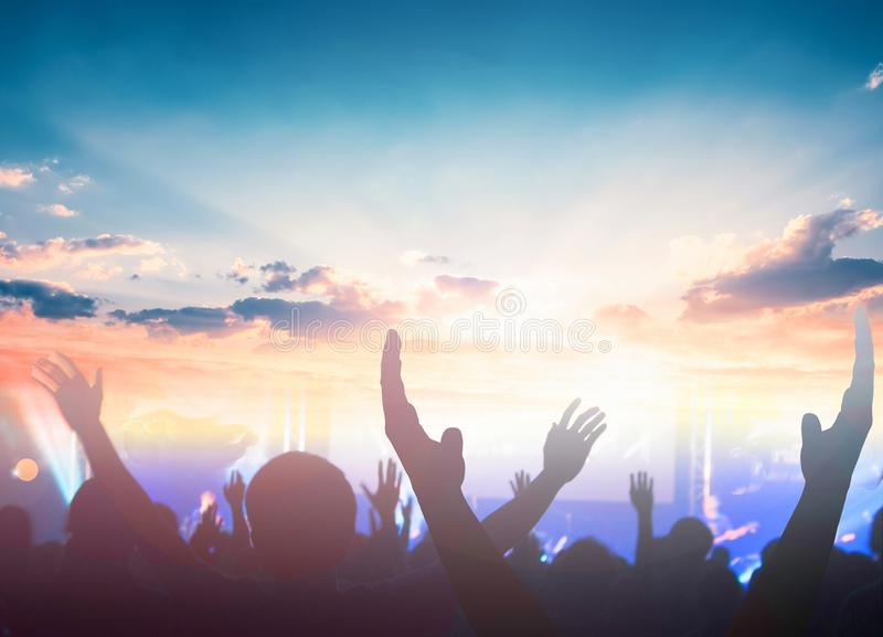 Worship and praise concept: christian people hand rising on sunset background. Hand Reach Sky In Silhouette Against Sunset royalty free stock images