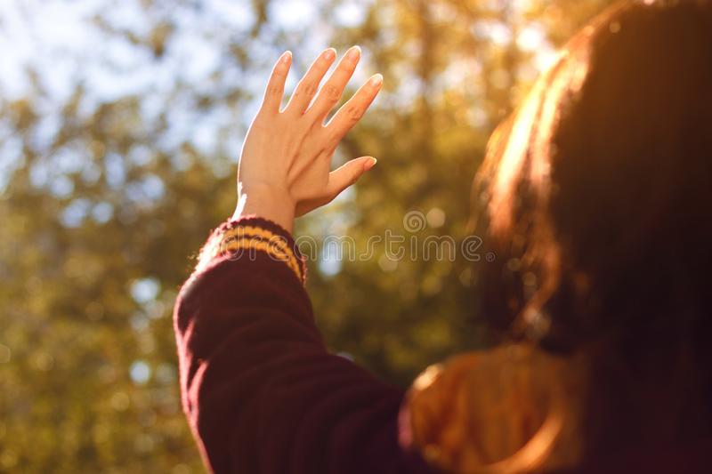 A hand reaches for the sky and covers the sun, the sun`s rays make their way through the hand royalty free stock image