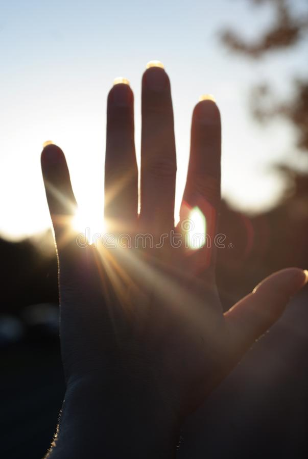 A hand reaches for the sky and covers the sun, the sun& x27;s rays make their way through the hand. stock photography