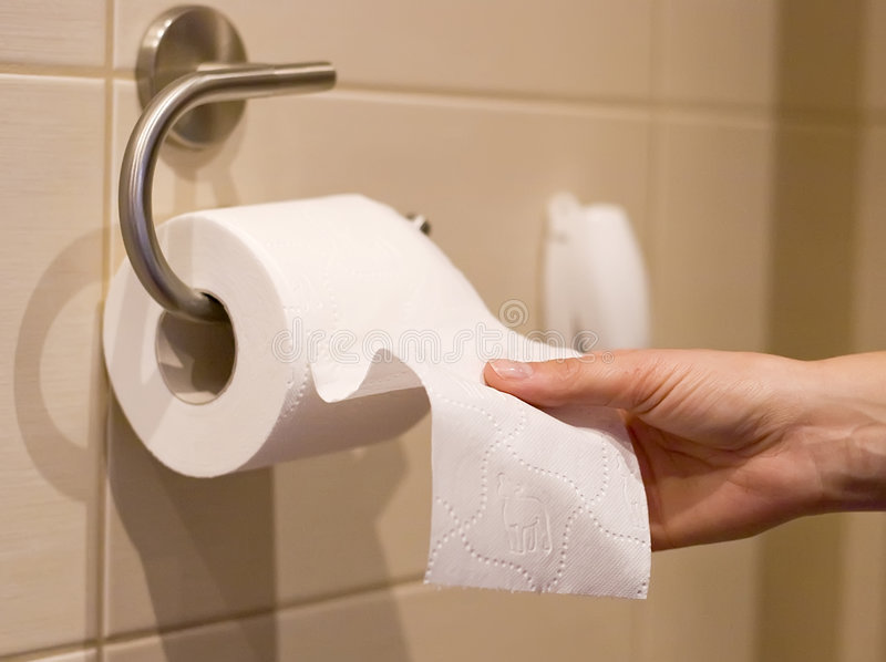Hand reaches for toilet paper stock photos