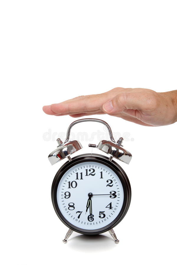 Hand reaching for alarm clock on white. A hand reaching for an old-fashioned alarm clock on a white background stock images