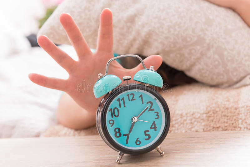 Hand reaching the alarm clock stock image