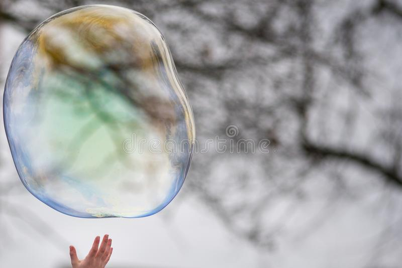 Chiilds hand reaches upwards to pop soap bubble with black and white pattern in background stock photography