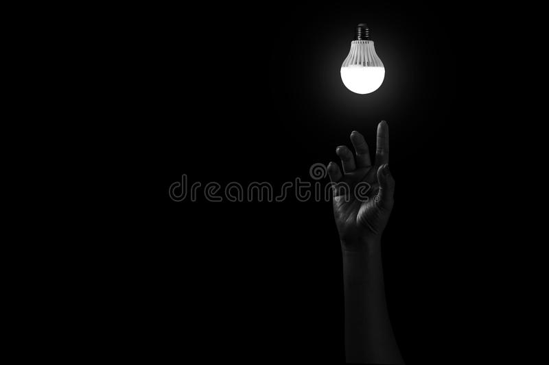 Hand reaching out to light in black,. Hopeful concept in white tone stock photo