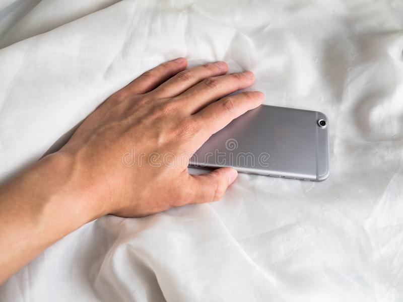 Hand reaching for phone in the bed royalty free stock photography