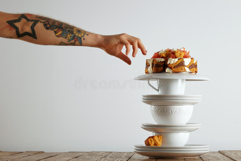 Hand reaching for piece of cake royalty free stock photography
