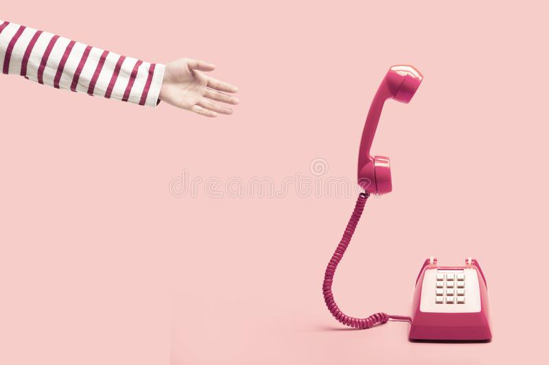 Hand reaching to the pink retro telephone stock photos