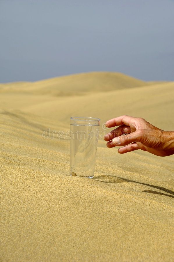 Hand reaching for water. Hand is reaching for a fresh glass of cold water in desert royalty free stock photos