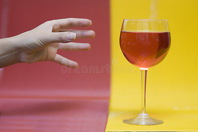 Hand reaching for wine glass. Hand reaching for glass of wine on yellow and red background stock photo