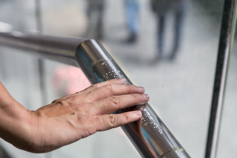 Hand reading Braille inscriptions for the blind on public amenity railing stock image