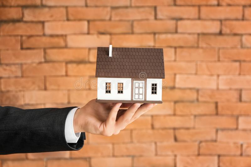 Hand of real estate agent with house model against brick wall. Mortgage concept royalty free stock image