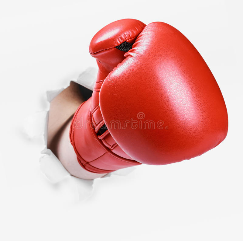 Hand in a red boxing glove broke through the paper wall. Place an empty paper for your text royalty free stock photo