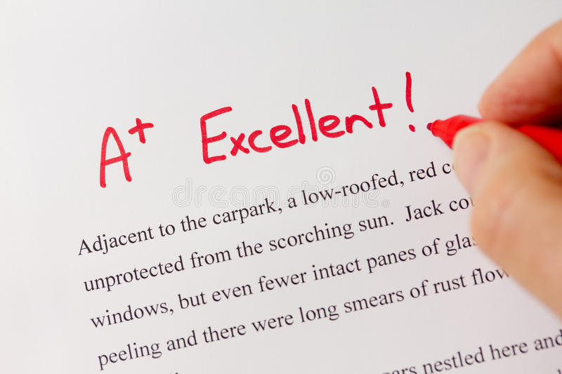 Hand with Red Pen Grading Successful Essay with Excellent royalty free stock photo