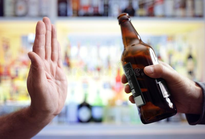 Hand rejecting alcoholic beer beverage. Concept for alcoholism and addiction royalty free stock photo
