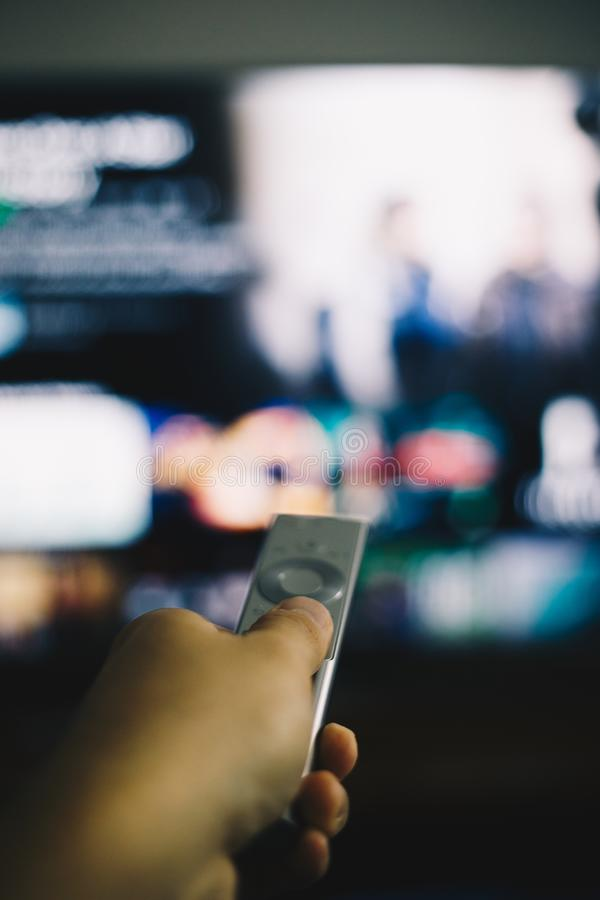 Hand with remote changing television channel royalty free stock photography