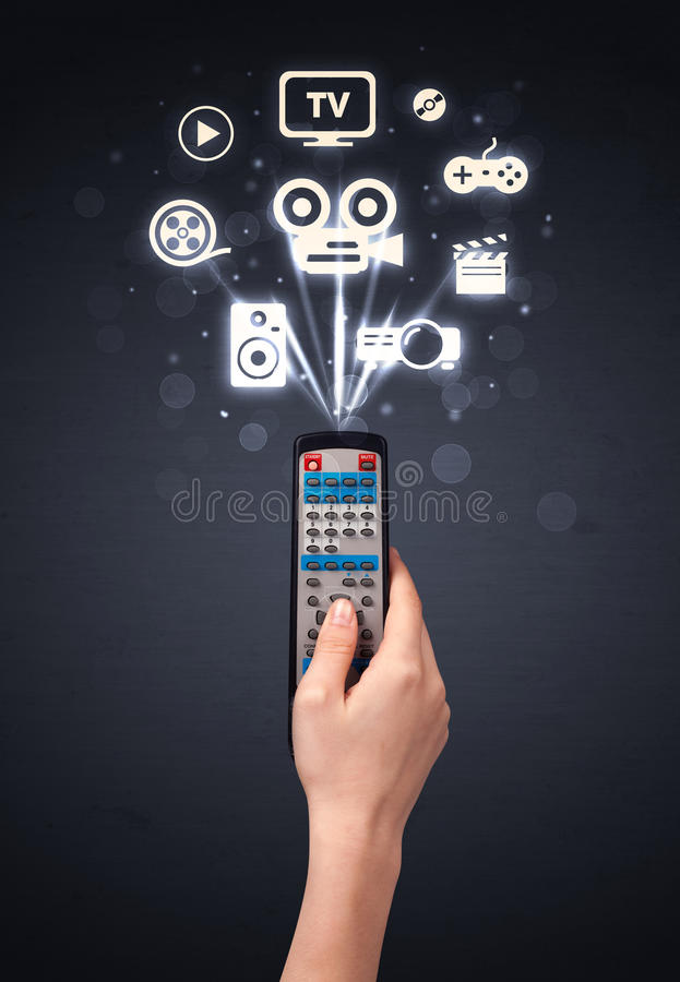 Hand with remote control and media icons. Hand holding a remote control, media icons coming out of it stock images