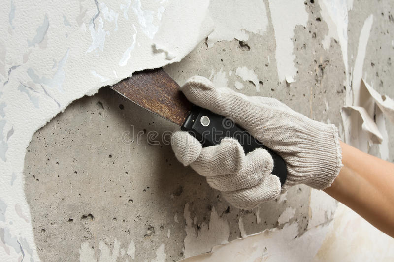 Hand removing wallpaper from wall with spatula. Hand removing old wallpapers from wall with spatula during repair royalty free stock image