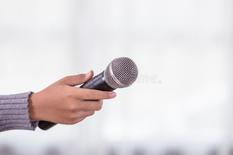 Hand of reporter holding new black microphone stock photos