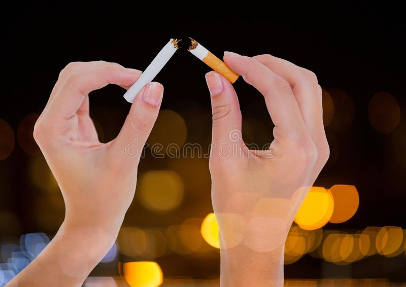 Hand ripping cigarette to quit smoking with sparkling light bokeh background. Digital composite of Hand ripping cigarette to quit smoking with sparkling light royalty free stock images