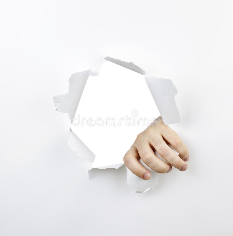 Hand Ripping Through Hole In Paper Stock Photography