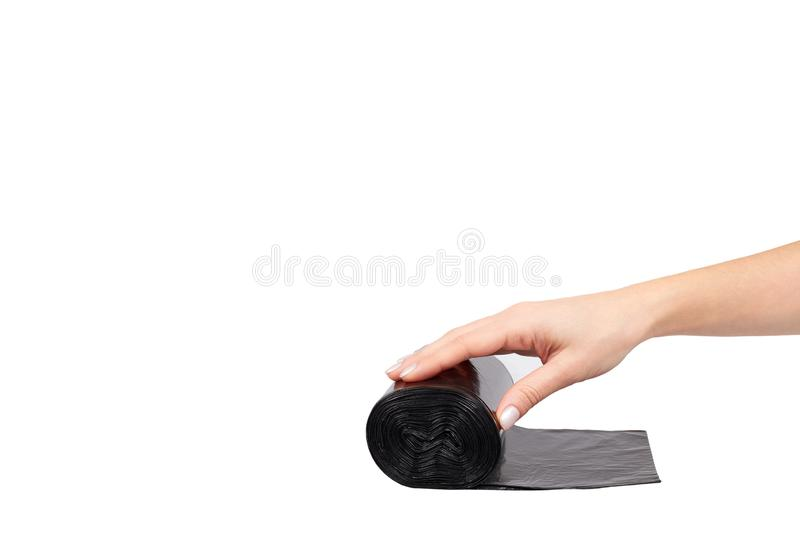 Hand with roll of black plastic garbage bags for trash. Isolated on white background. Copy space bin clean container dump dustbin housework neat new packet stock photo