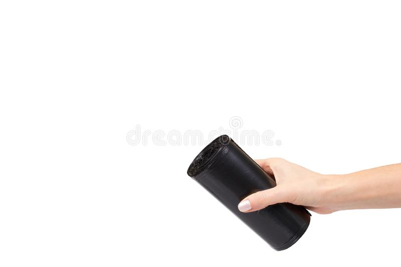 Hand with roll of black plastic garbage bags for trash. Isolated on white background. Copy space bin clean container dump dustbin housework neat new packet stock image