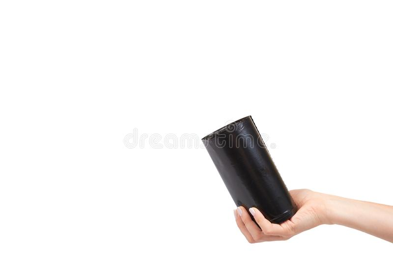 Hand with roll of black plastic garbage bags for trash. Isolated on white background. Copy space bin clean container dump dustbin housework neat new packet stock photos