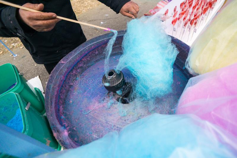 Hand rolling cotton candy in candy floss machine. Candyfloss making royalty free stock photos