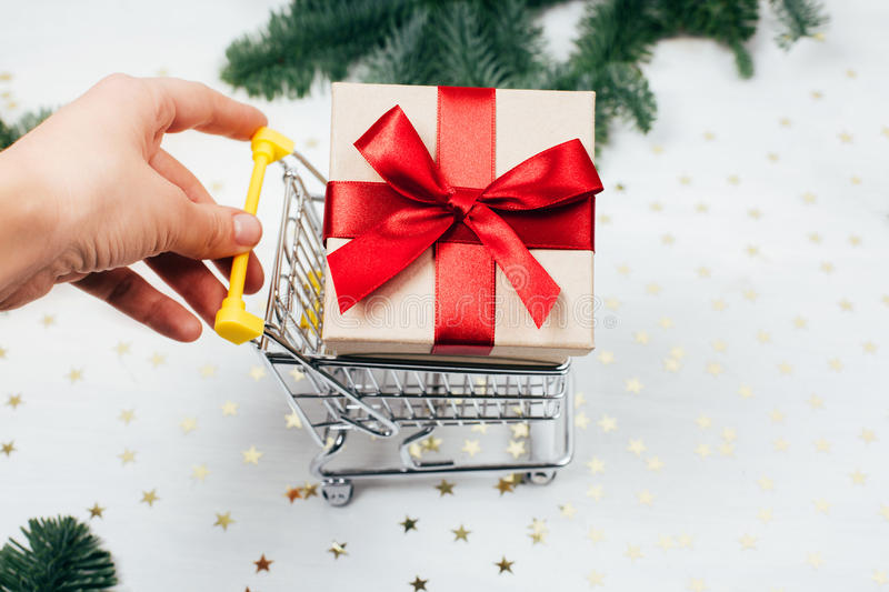 Hand rolls shopping basket with a gift. Hand rolls shopping cart with a gift. Concept of bying Christmas present stock photo
