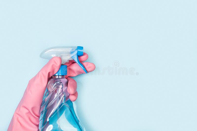Hand with rubber glove holding a cleaning product sprayer. On a light blue background royalty free stock image
