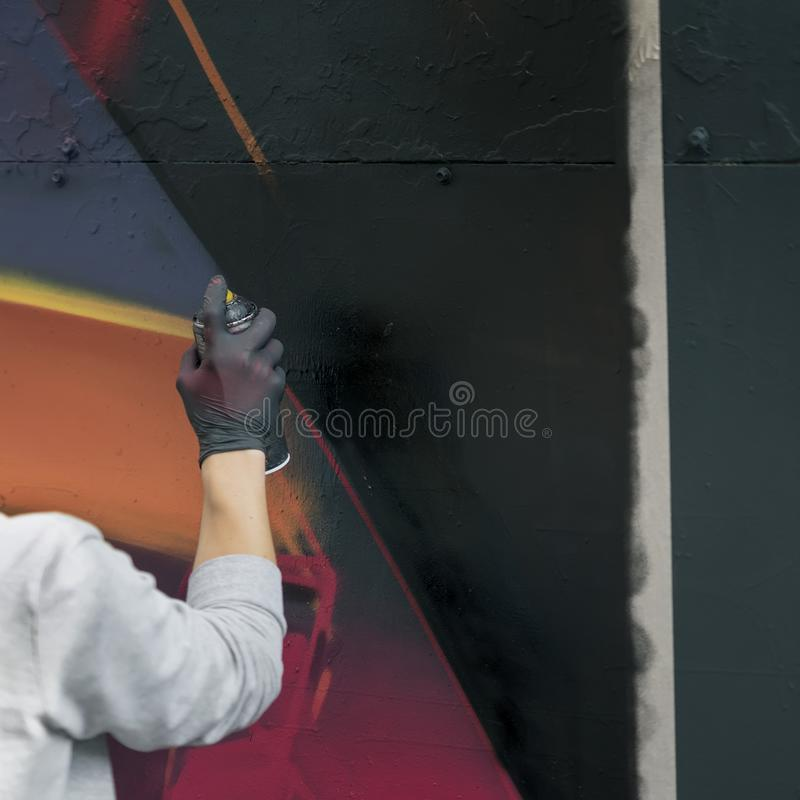 Hand in rubber glove of teenager, young urban painter drawing graffiti on wall. Modern iconic urban culture of youth royalty free stock photos