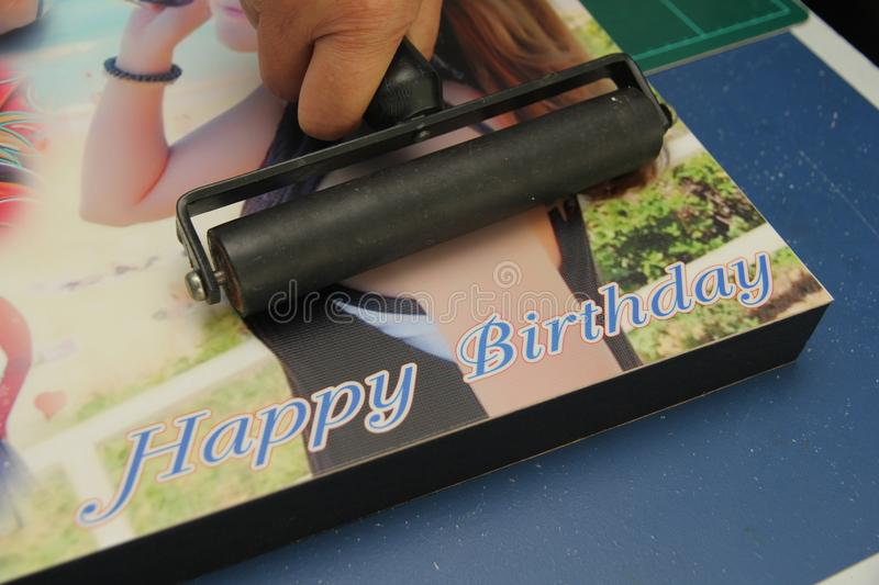 Hand Rubber Roller to be rolling Photo paper on board by glue us. Photo Floating frame building in canvas art ,Hand Rubber Roller to be rolling Photo paper on royalty free stock photo