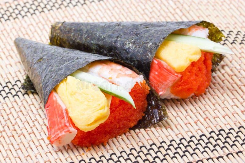 Hand rullande traditionell japansk kokkonst för Temaki sushi. arkivfoto