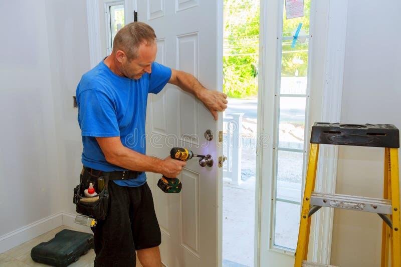 Hand & x27; s de mens met schroevedraaier installeert deurknop stock foto's