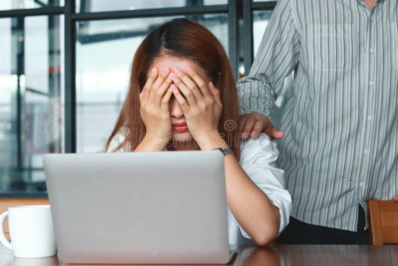 Hand ` s van collega troostende gedeprimeerde droevige Aziatische vrouw met handen op gezicht die op de werkplaats in bureau schr royalty-vrije stock afbeeldingen