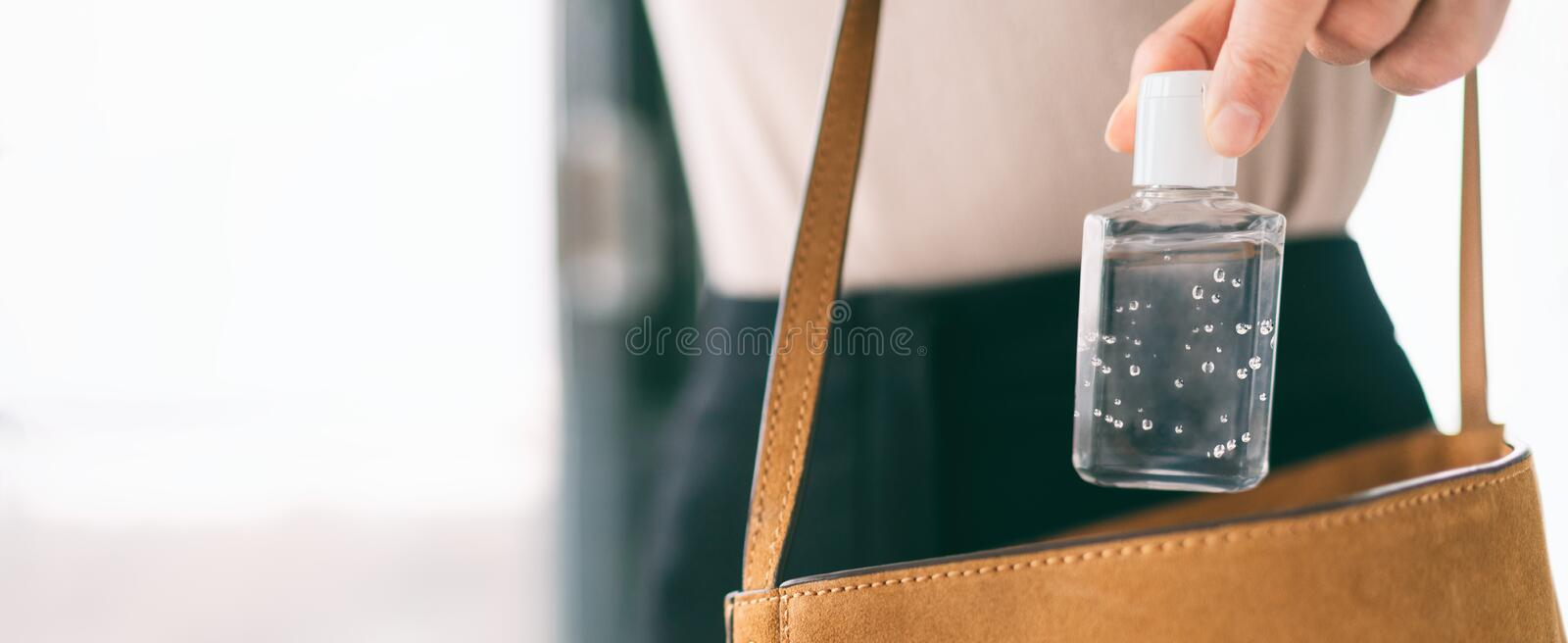 Hand sanitizer travel bottle woman carrying in purse COVID-19 prevention alcohol gel for cleaning hands while outside royalty free stock photo
