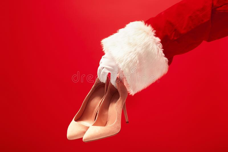 Hand of Santa Claus holding a women`s shoes on red background royalty free stock photo