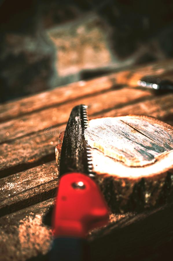 A hand saw cuts a piece of wood from a round beam and pines on a bench. Around the wreckage and sawdust. A wooden stand for food royalty free stock images