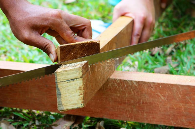 Hand saws sawing the wood. stock images