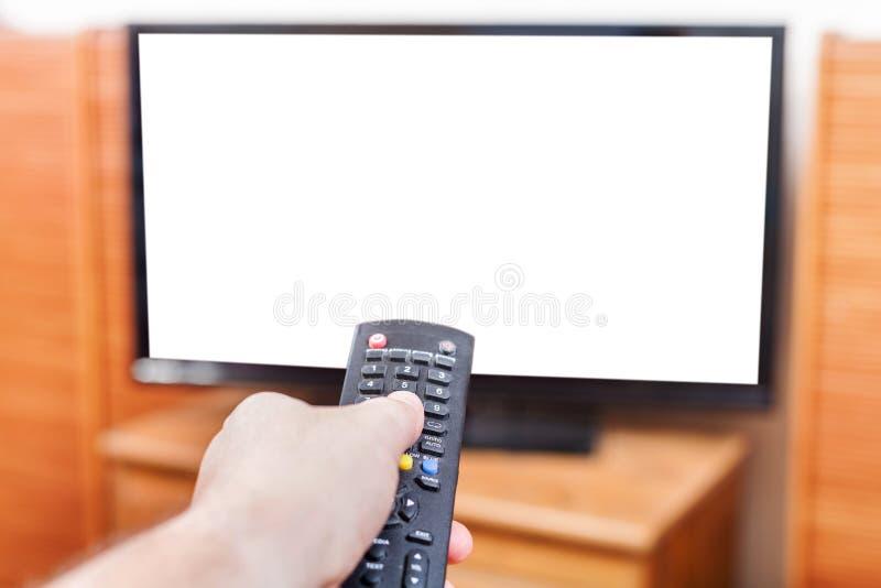 Hand schaltet Fernsehkanäle mit herausgeschnittenem Schirm lizenzfreie stockfotografie