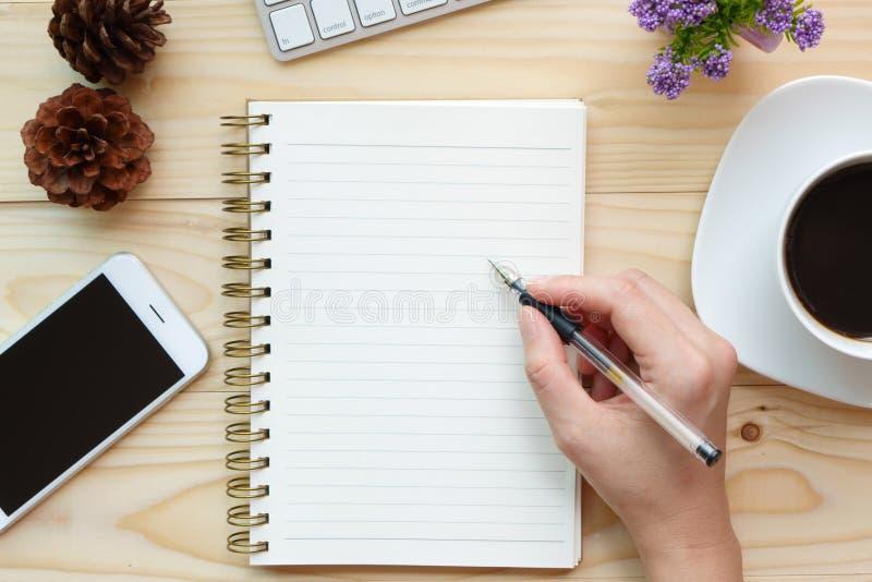 Hand schreiben auf Notizbuch auf hölzernem Arbeitsschreibtisch stockbild