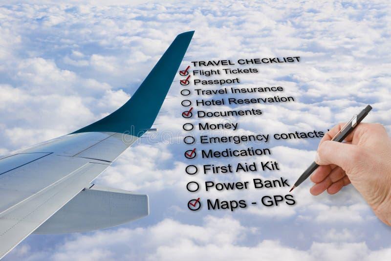 Hand schreiben eine Reise-Checkliste über einem bewölkten Himmel und einem Flugzeug - c lizenzfreies stockbild