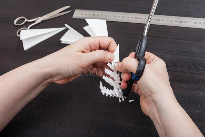 Hand with scissors cut snowflake from paper. Top view of hand with scissors cut a figure of snowflake from folded sheet of paper on dark brown wooden table royalty free stock photography
