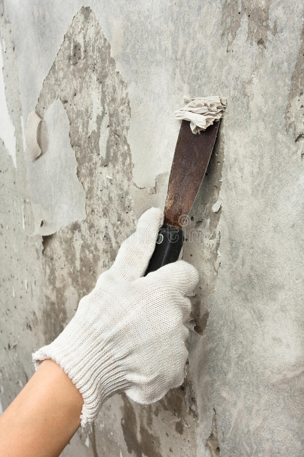 Hand scraping off old wallpaper with spatula stock image