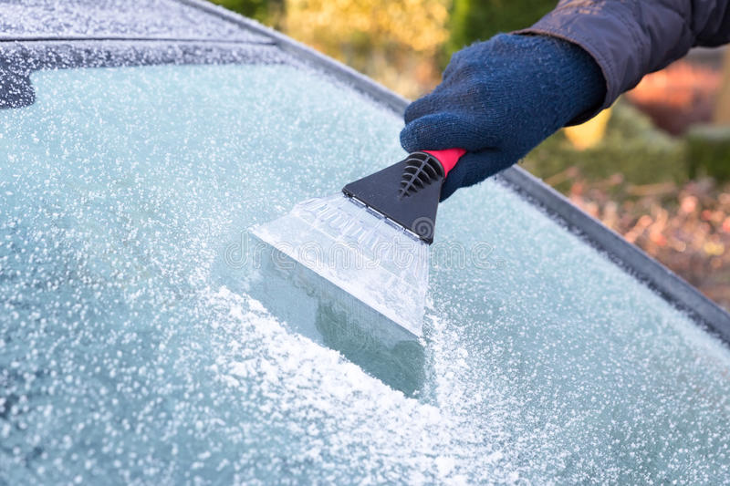 Hand scratching ice from car window royalty free stock photos
