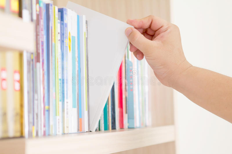 Hand selecting book from bookshelf royalty free stock photos