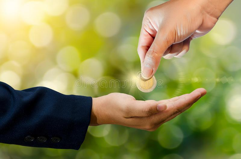 Hand send coin green bokeh background give money stock photos