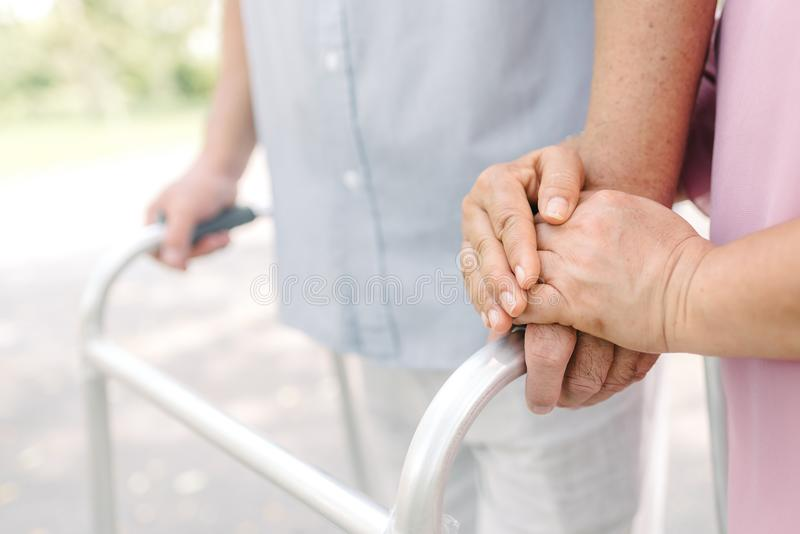 Hand of senior couple using walker in park. Hands of an elderly woman holding the hand of a elderly man while using walker in the park stock photo