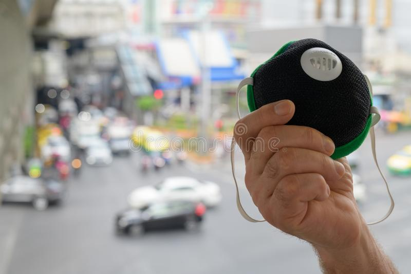 Hand of senior man holding face mask for protection from pollution smog in city. Senior man using mask to protect from pollution in city royalty free stock photos