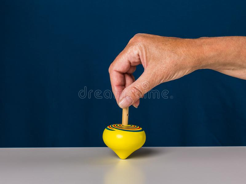 Middle aged woman playing spinning top. Wooden natural toys. stock image